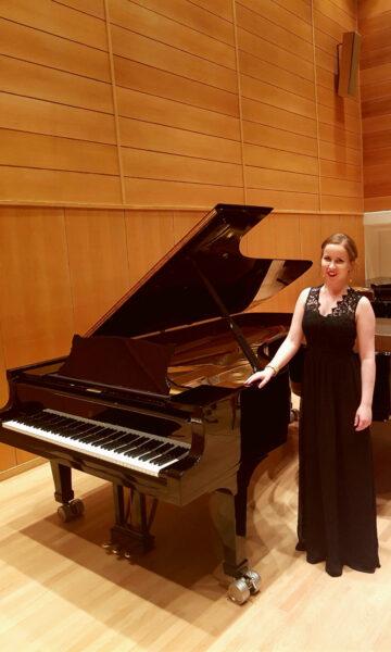 Nainen pianon edessä.