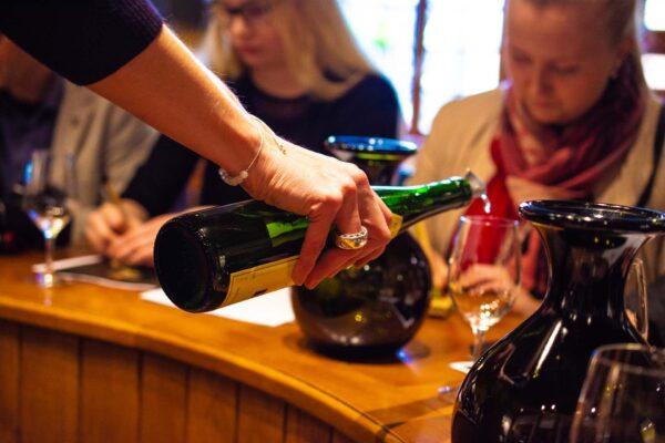Ravintolapöytä jossa kaadetaan viiniä lasiin.