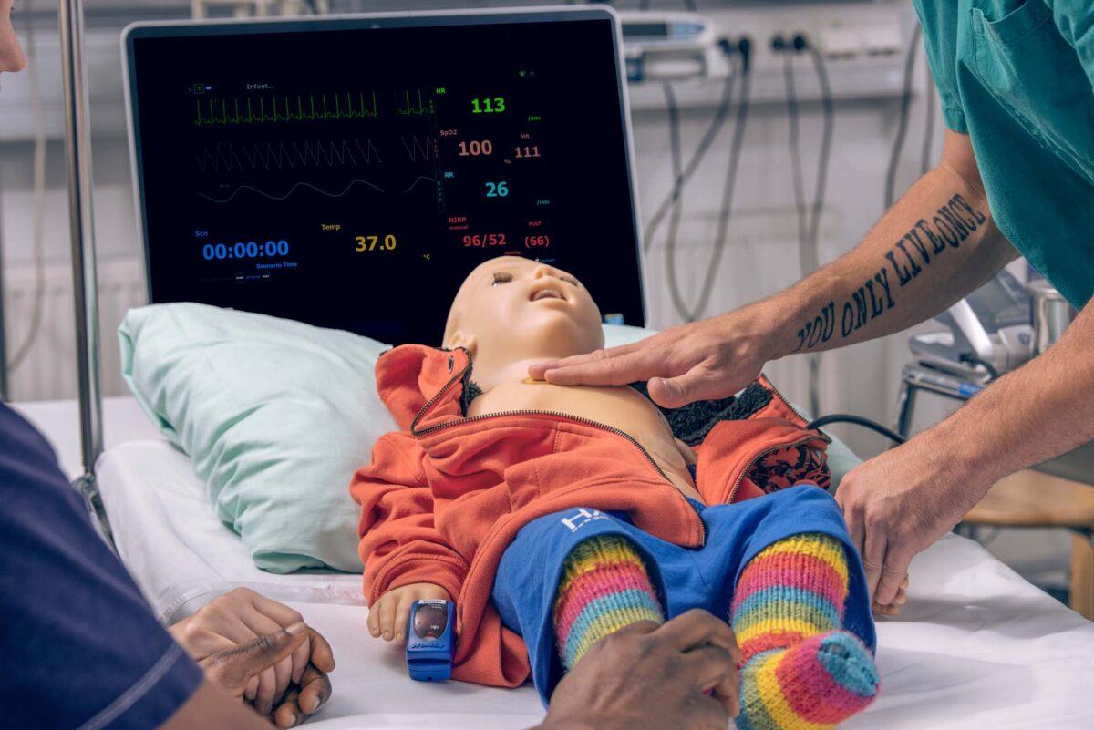 Hoitajan käsi ja lapsinukke.