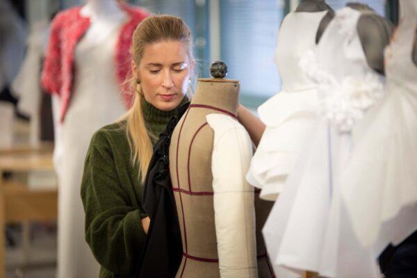 Vaatetusmuotoilun opiskelija pukemassa mallinukkea.