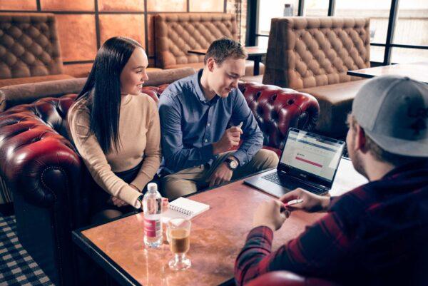 Nainen ja kaksi miestä ravintolassa keskustelemassa.
