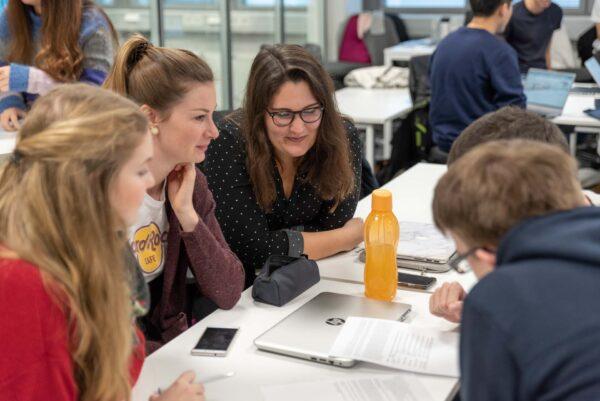 Opiskelijoita luokkatilassa, pöytien ääressä.