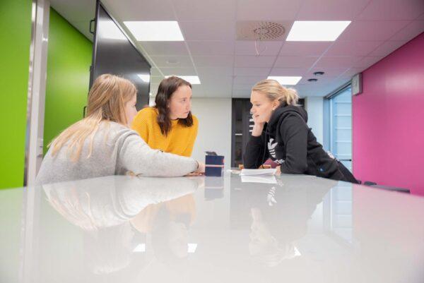Kolme opiskelijatyttöä pöydän ääressä.