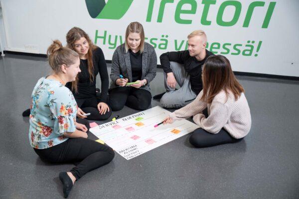 Opiskelijat istuvat lattialla ja suunnittelevat mindmapia.