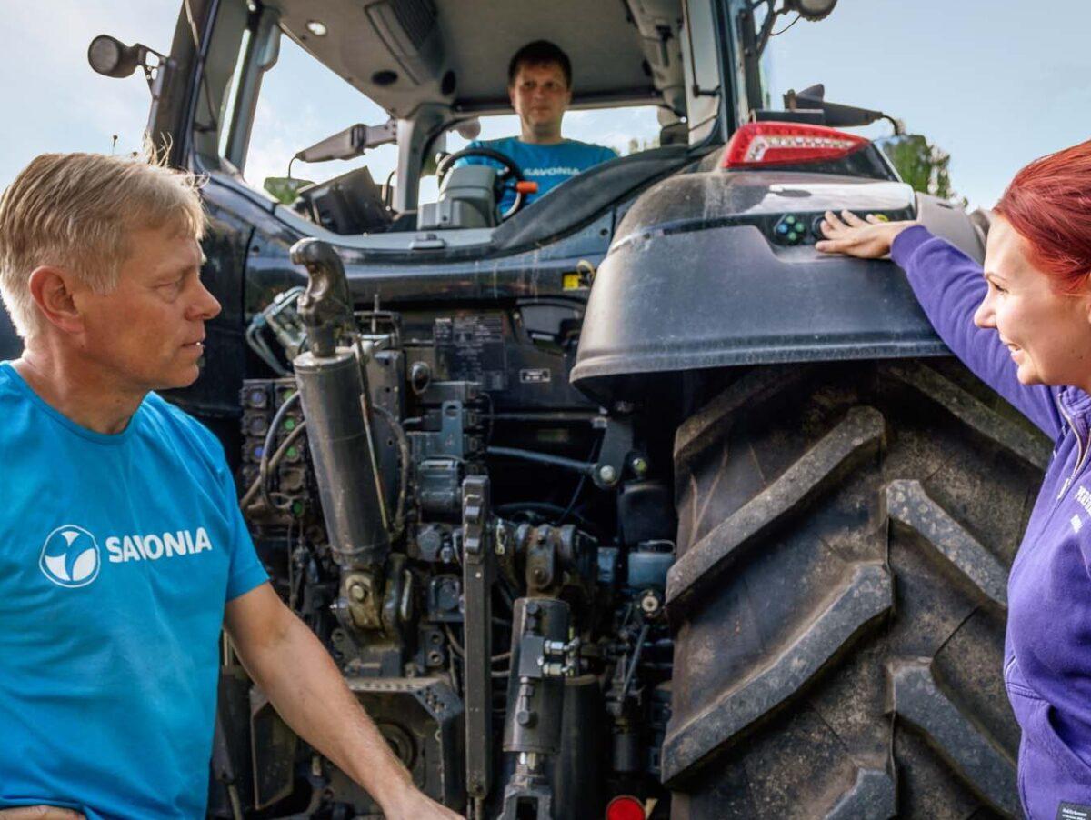 Mies traktorissa ja kaksi ihmistä traktorin vieressä.
