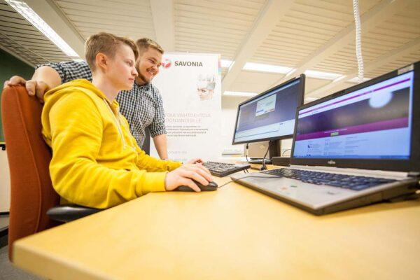 Kaksi opiskelijaa tietokoneen äärellä.