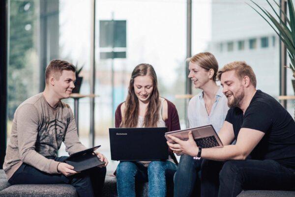 Nuoria ihmisiä istumassa tietokoneiden kanssa.
