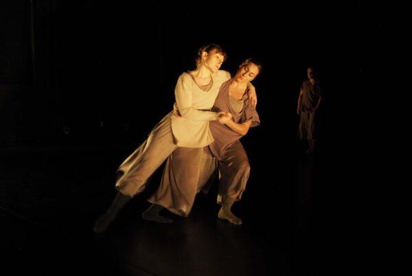 Kaksi naista tanssii pimeällä lavalla.