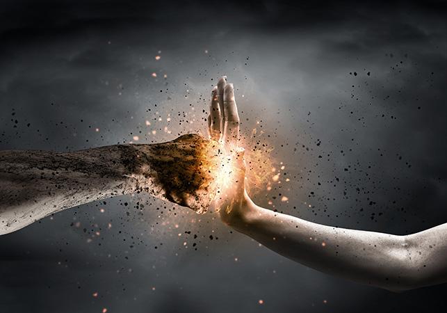 Avoin käsi torjuu nyrkin iskun, kipinöintiä käsien välissä