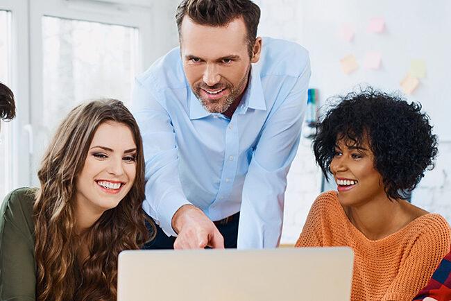 Ryhmä ihmisiä työskentelevät tietokoneella.