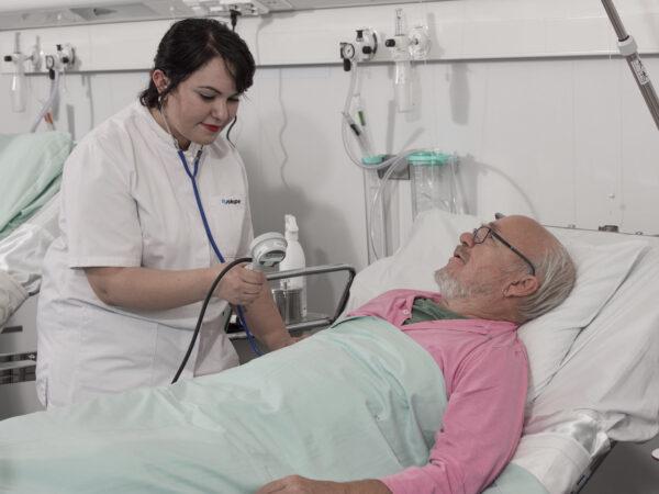 Kuvassa sairaanhoitaja on ikääntyneen miespotilaan äärellä sairaalan huoneessa. Potilas makaa sängyssä selällään yllään vaaleanpunainen sairaalakaapu.