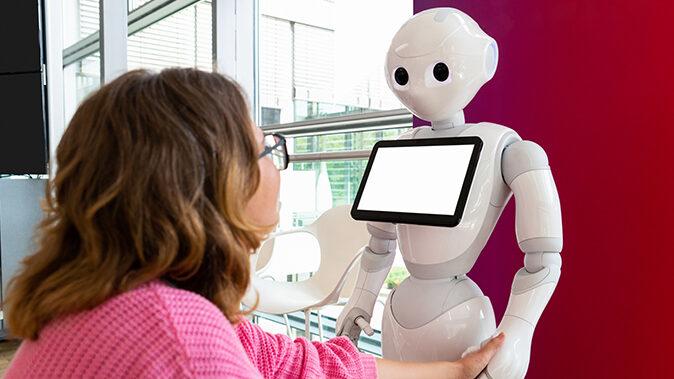 Nainen kättelee Pepper-robottia