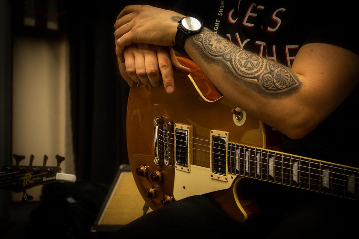 Kitaristi nojaa kitaraansa. Kuvassa näkyy vain kitaristin tatuoidut kädet ja kello.