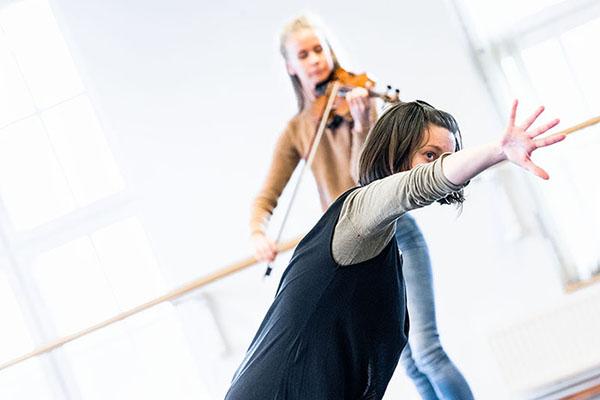 Tanssija kurottaa eteenpäin. Takana näkyy viulisti
