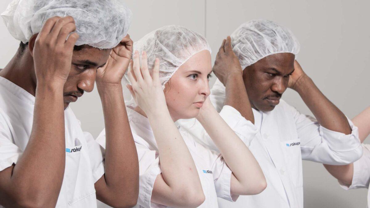 Hoitajat laittamassa hiussuojaa päähän.