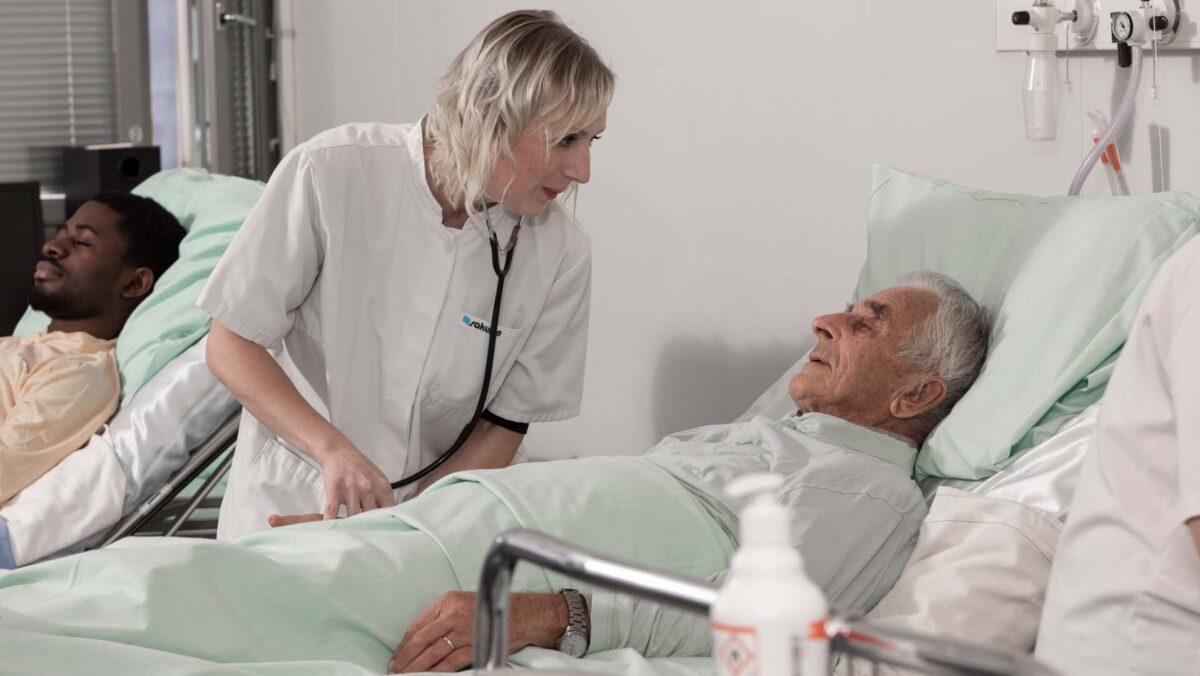 Sairaanhoitaja on sairaalahuoneessa ikääntyneen potilaan äärellä. Potilas makaa sairaalasängyssä selällään.