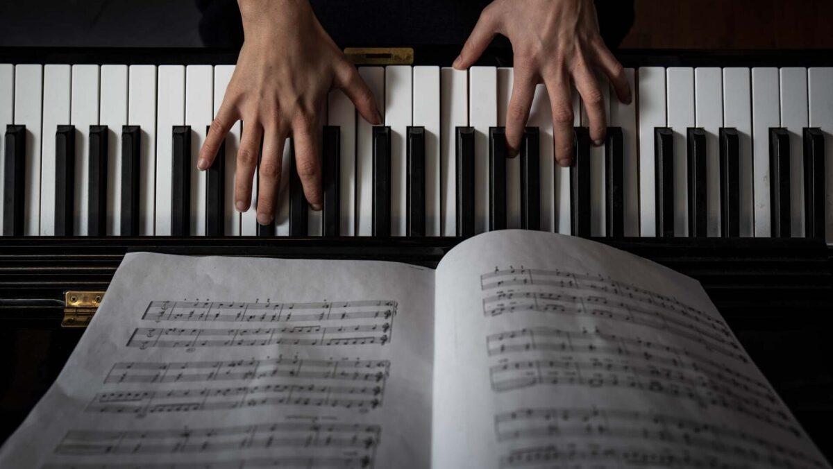 Sormet pianon koskettimilla.