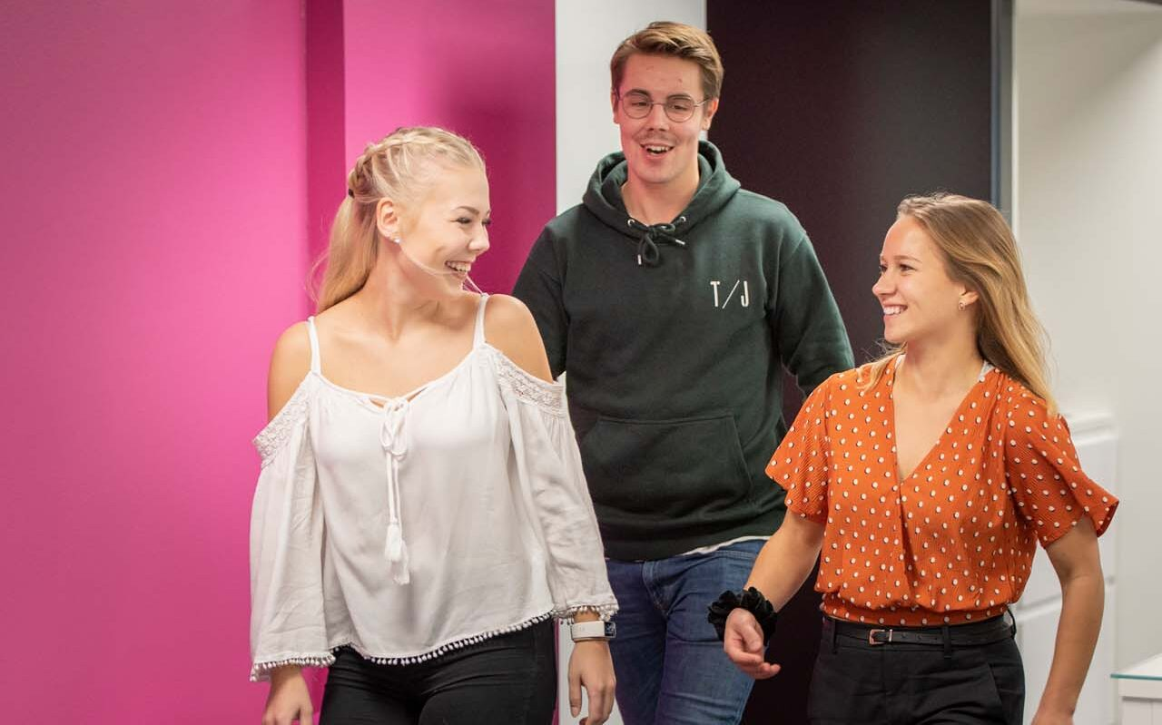 Finnish students walking and laughing in a corridor with pink background.