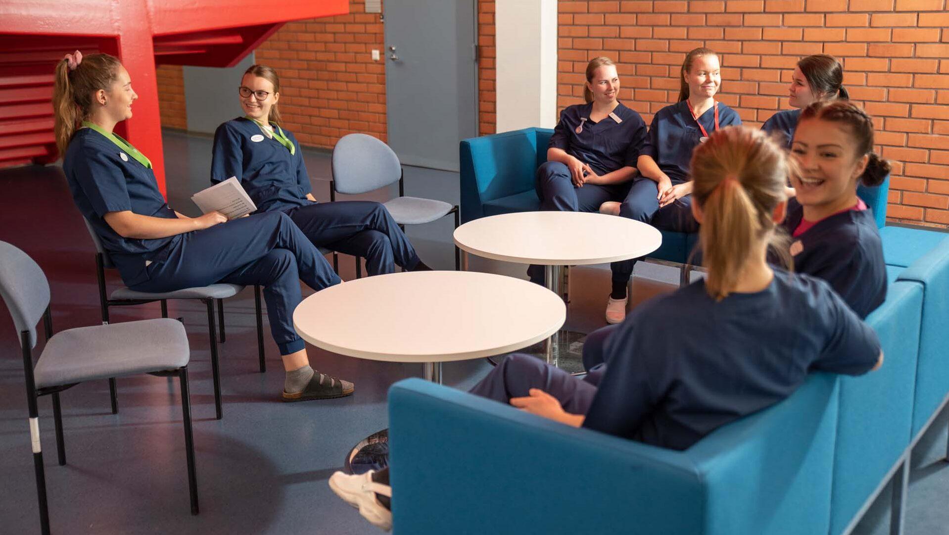 Hoitotyöntekijöitä istuu sohvaryhmässä.