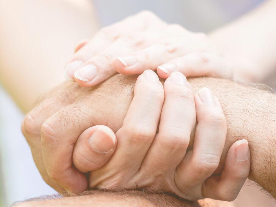 Nuoren kädet pitelevät vanhuksen kättä.