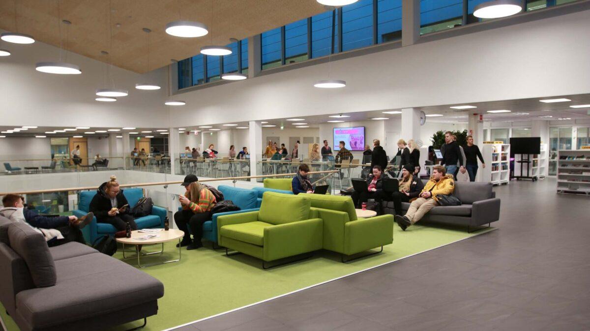 Ihmisiä istumassa kirjastossa.