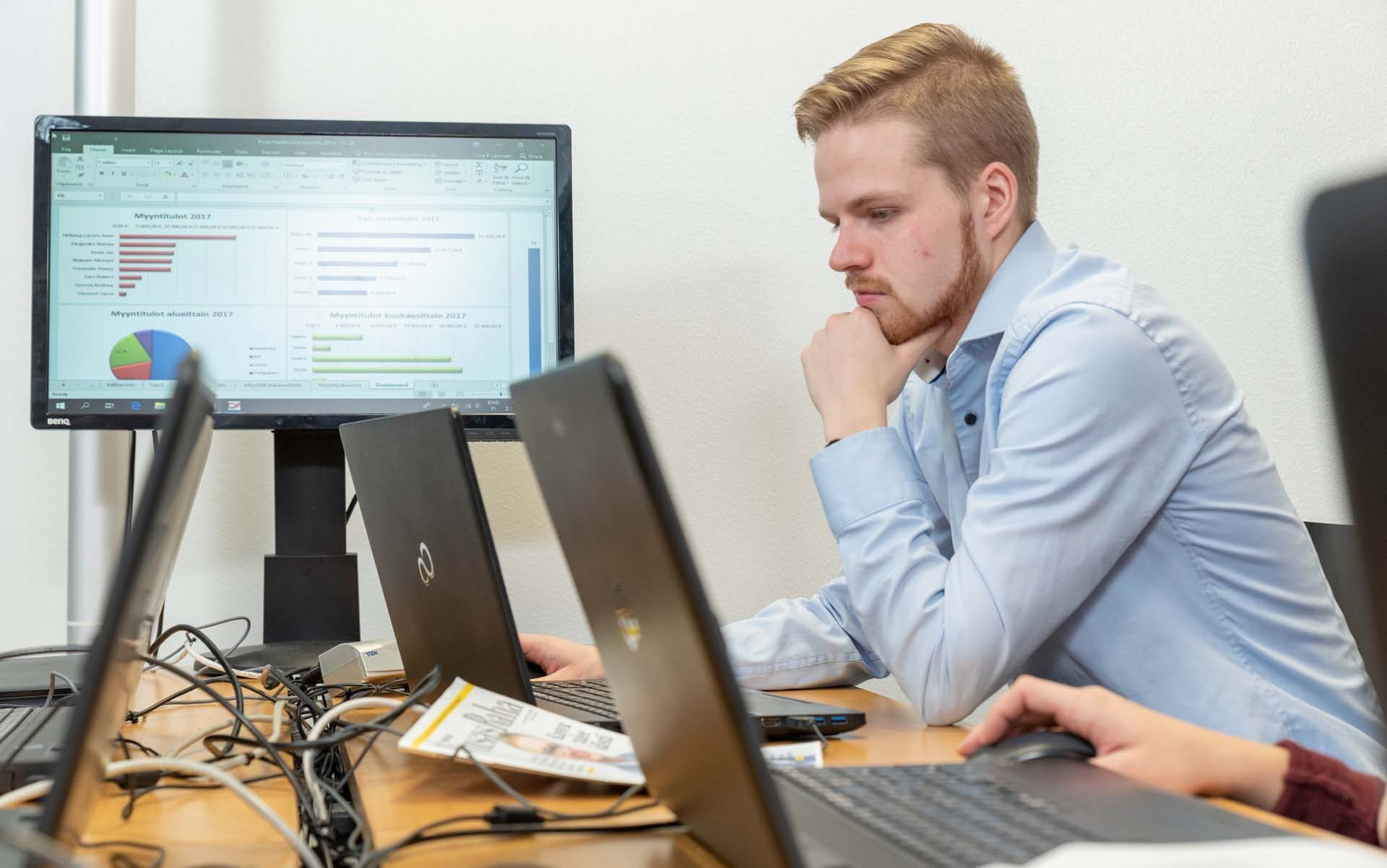 Man sitting in front of a laptop thinking and looking at its screen.