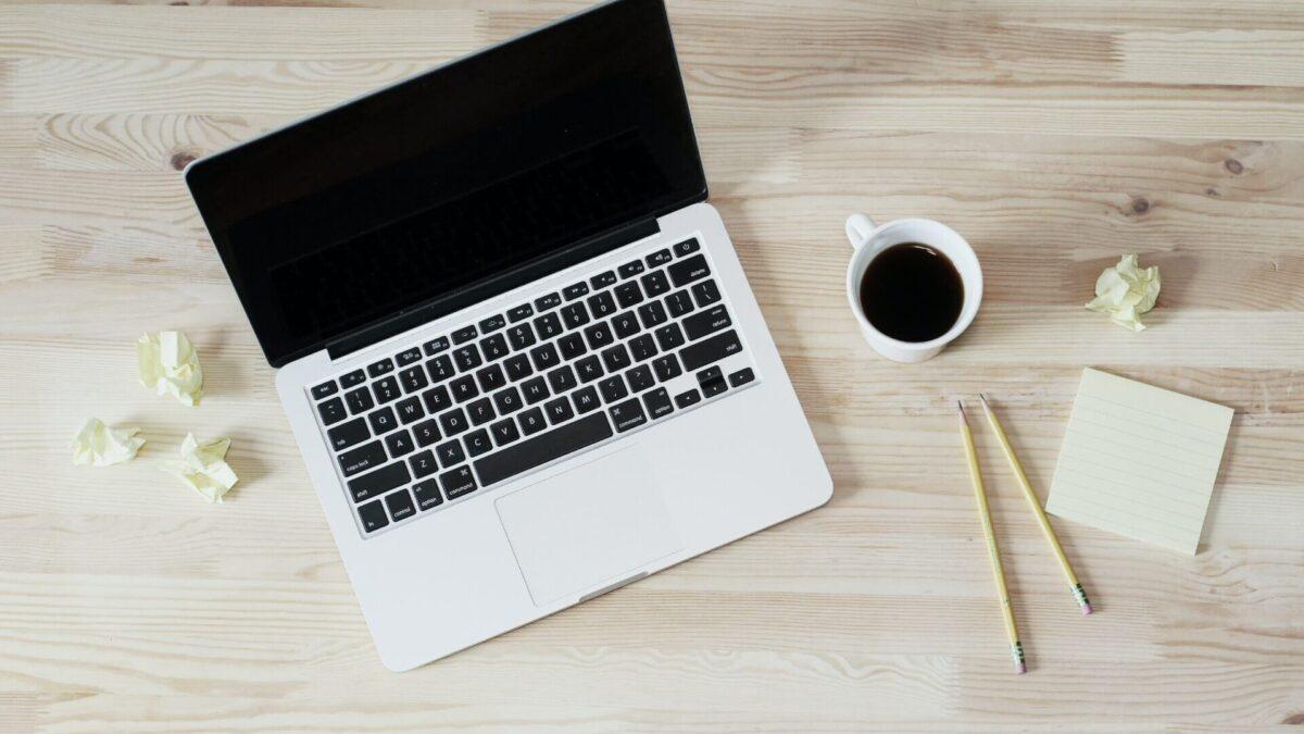 Kannettava tietokone ja kahvikuppi pöydällä.