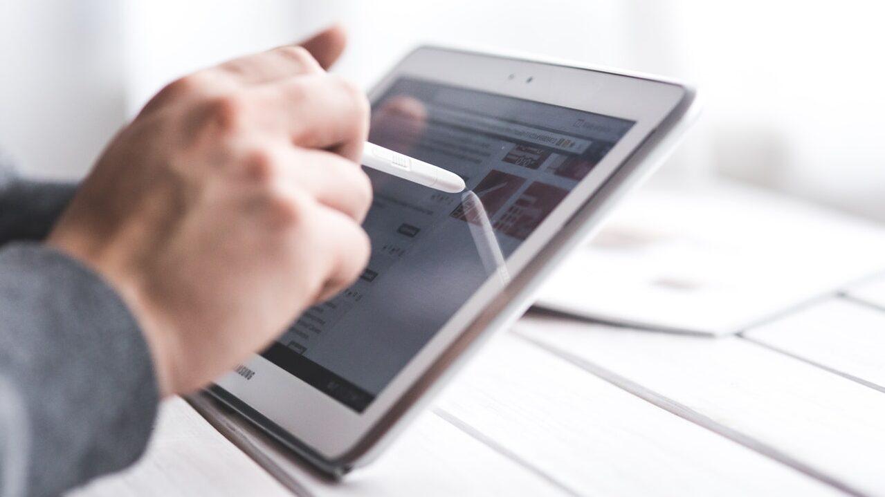 Henkilö koskettaa tablet-tietokonetta.