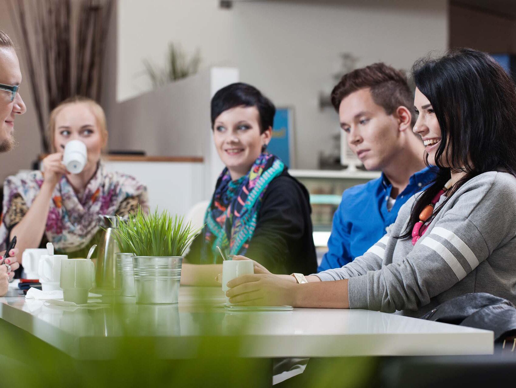 Henkilöitä istuu pöydän ääressä.