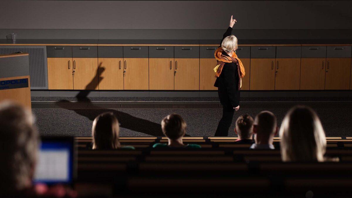 Nainen esitelmöi auditoriossa.