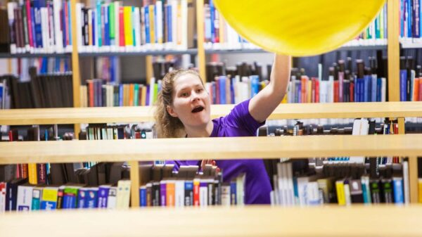 Nainen heittää kirjastossa palloa.