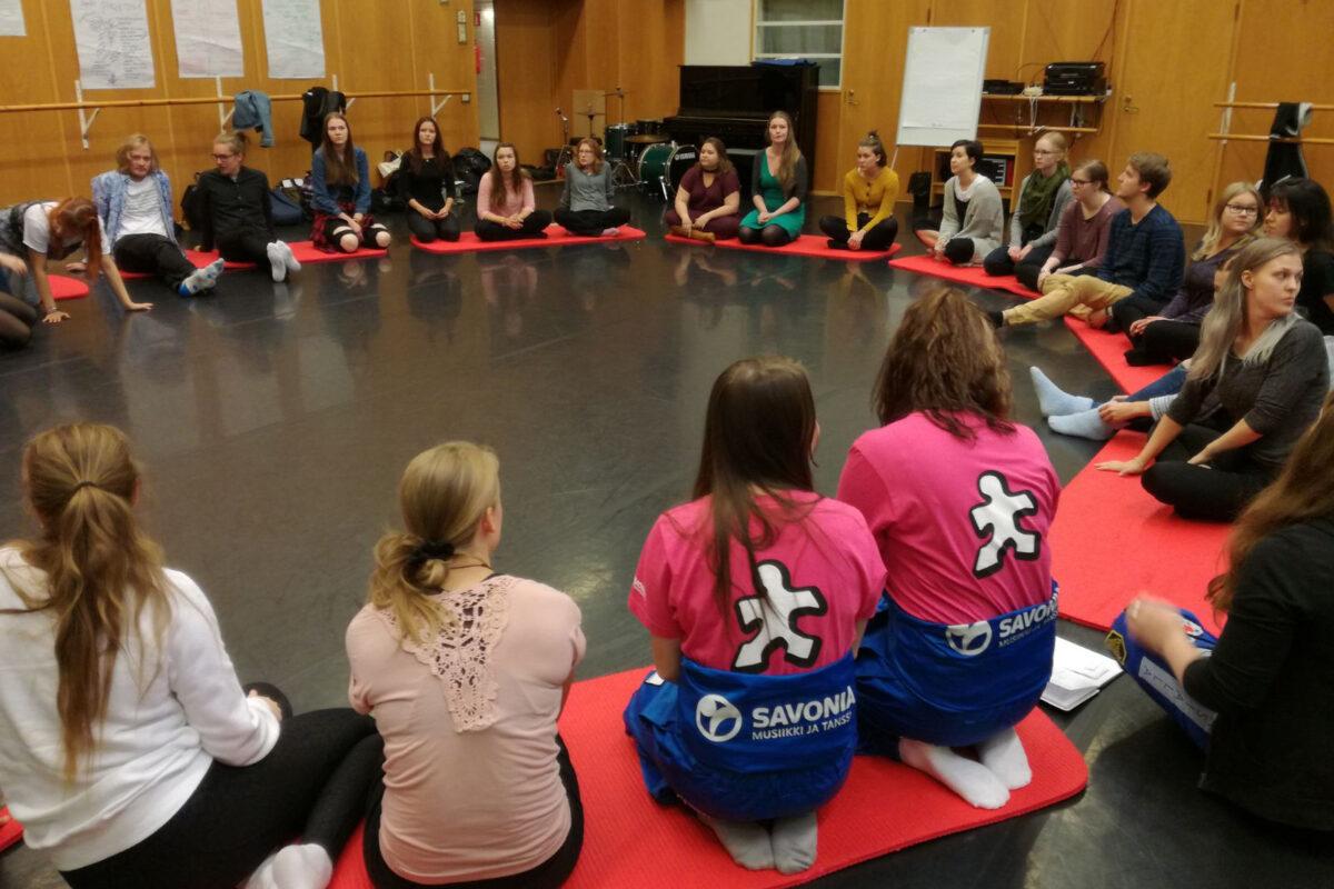 Tuutorit istuvat uusien opiskelijoiden kanssa ringissä.