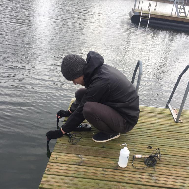 Ympäristötekniikan opiskelija laiturilla tutkimassa vettä.