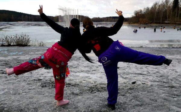 Kaksi tyttöä opiskelijahaalareissa talvisella rannalla.