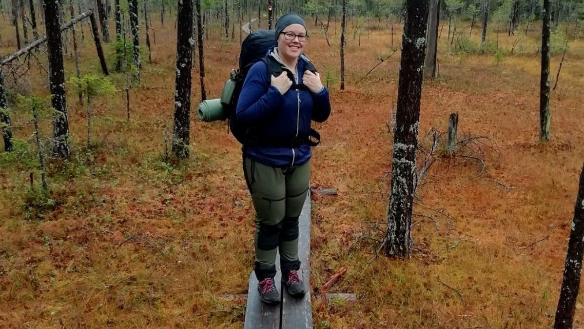 Nainen rinkka selässä pitkospuilla metsässä.