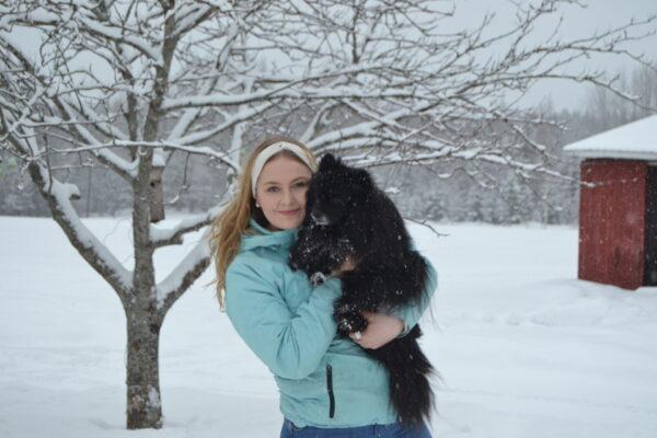 Nuori nainen koira sylissä talvimaisemassa.
