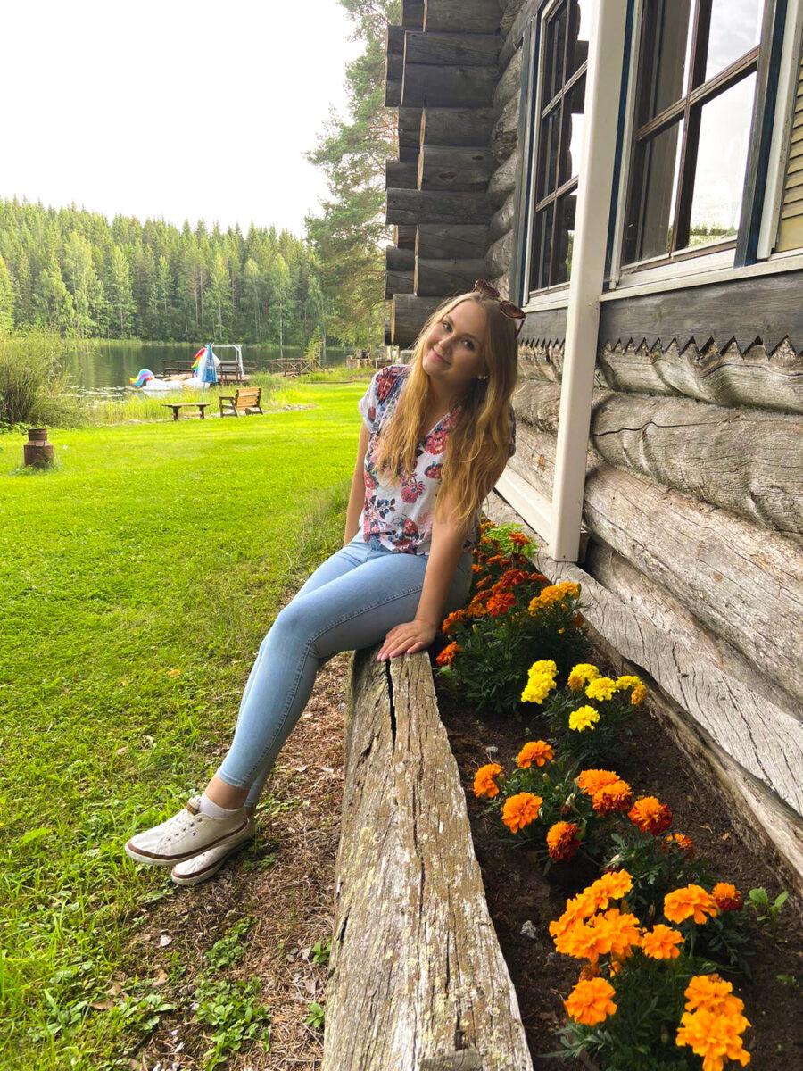 Nuori nainen istumassa hirsimökin seinustalla.