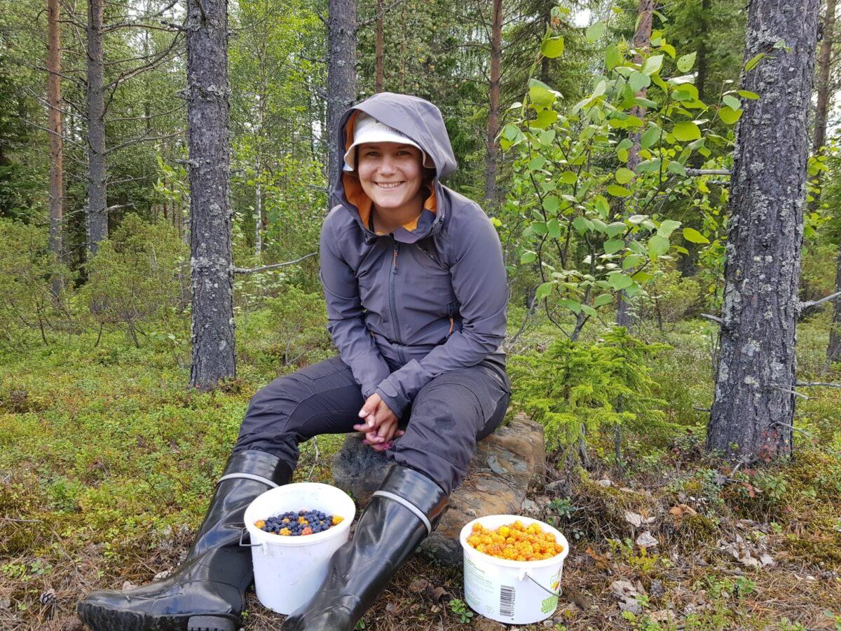 Nainen istumassa kivellä metsässä marjasankkojen kanssa.