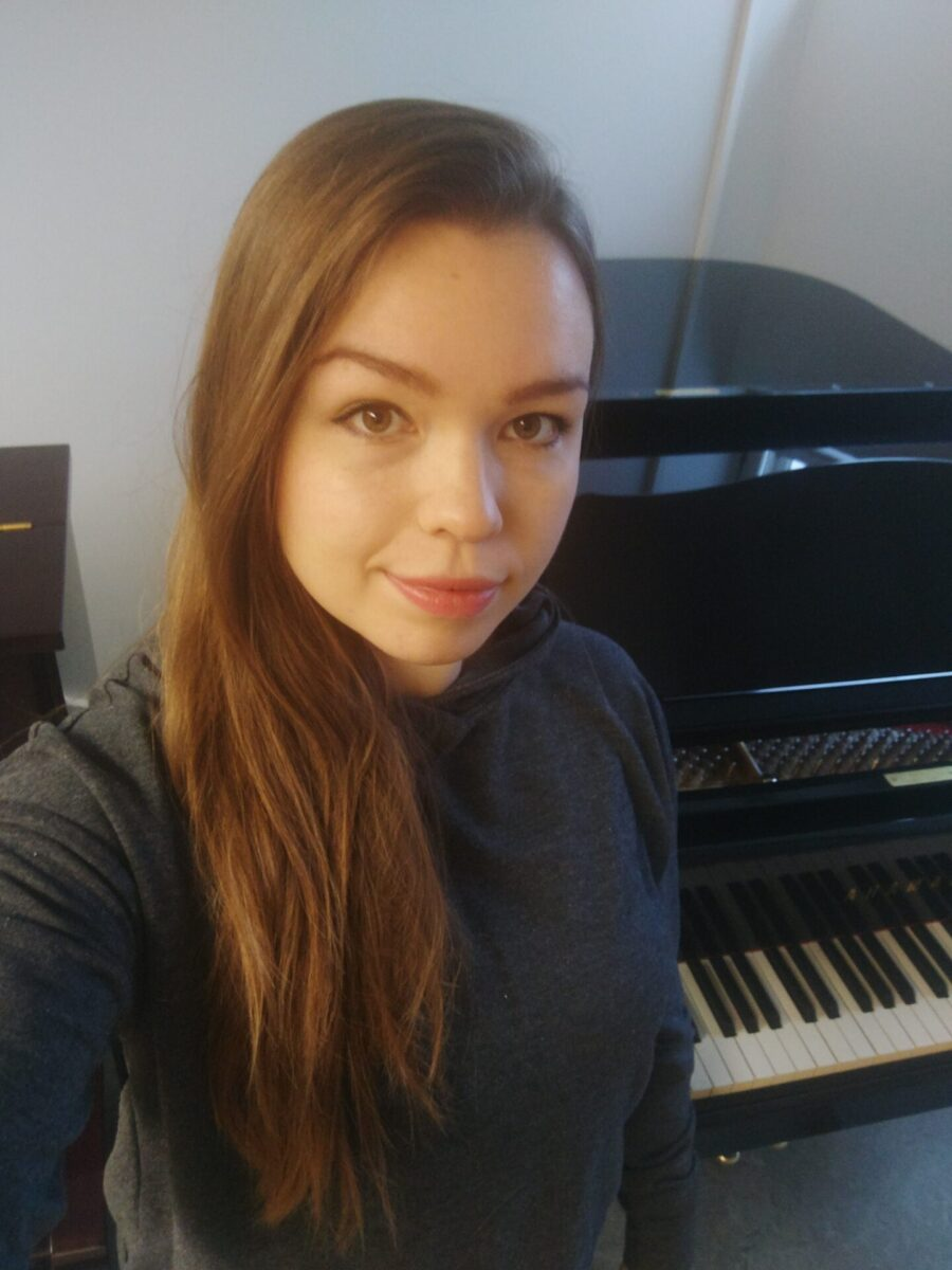 Nainen seisomassa pianon ääressä.