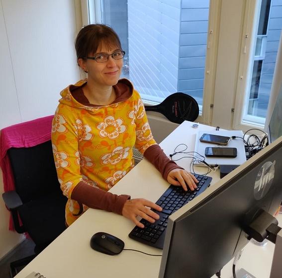 Erja Eskelinen istuu tietokoneen äärellä toimistoympäristössä. Hänellä on yllään keltanen pusero ja hän katsoo hymyillen kameraan.