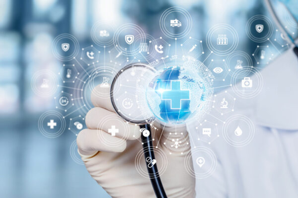 Picture of the hand of a doctor holding a stethoscope in the back of a small blue Earth globe