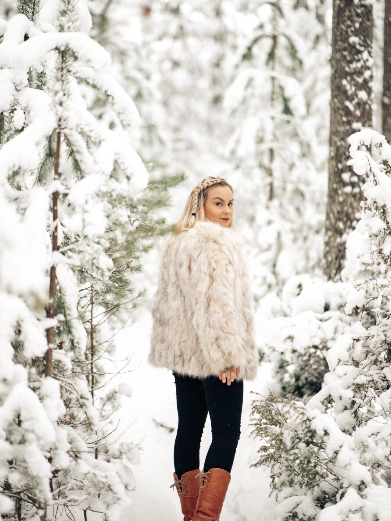 Vaaleahiuksinen nainen kävelemässä turkki päällä lumisessa metsässä.