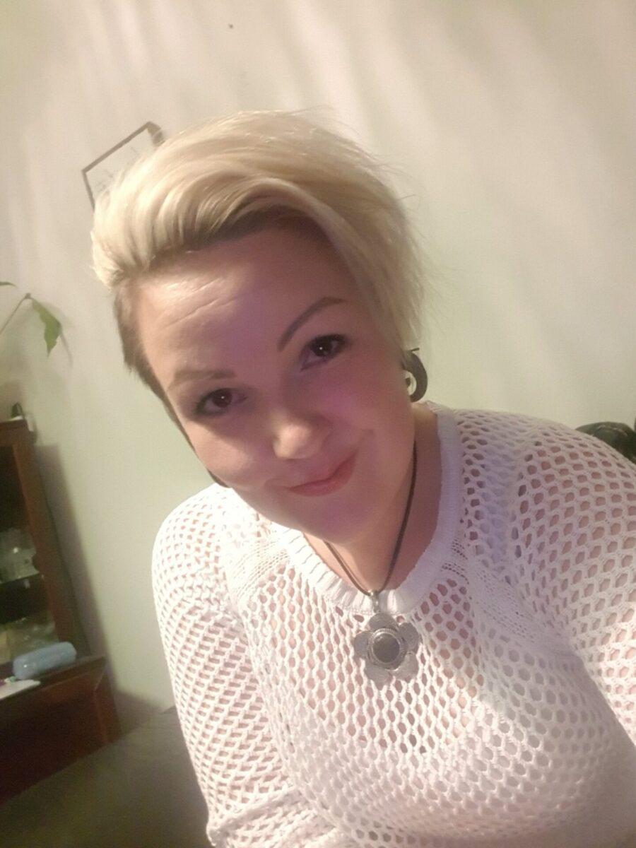 Hymyilevä vaaleatukkainen nainen lähikuvassa sisätilassa.