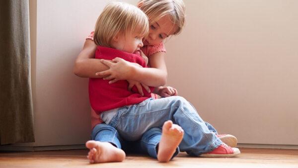 Kaksi lasta istumassa lattialla