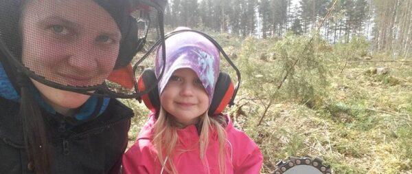 Nainen ja tyttölapsi moottorisahan kanssa metsätöissä.