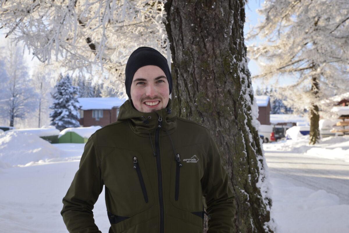 Nuori mies poseeraamassa pipo päässä puun edessä. Taustalla talvinen maisema.