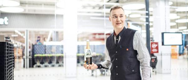 Markus Niskanen työpaikallaan Alkossa, seisoo sisäänkäynnin luona viinipullo kädessään hymyssä suin.