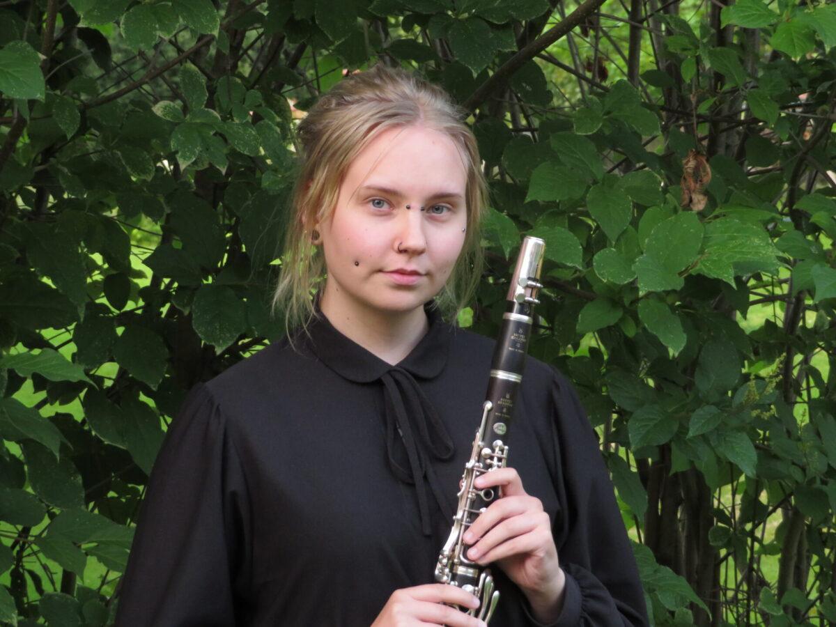 Nainen poseeraamassa ulkona klarinetin kanssa.
