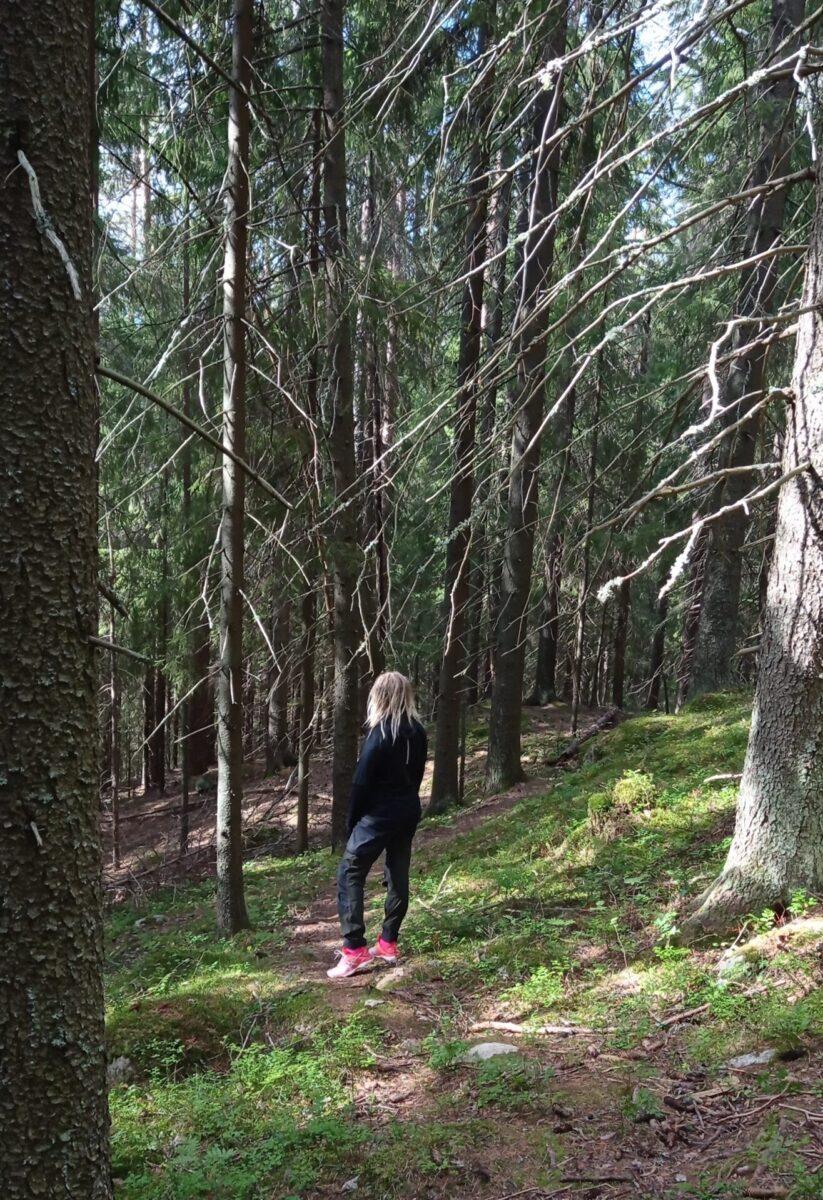 Nainen metsäpolulla.