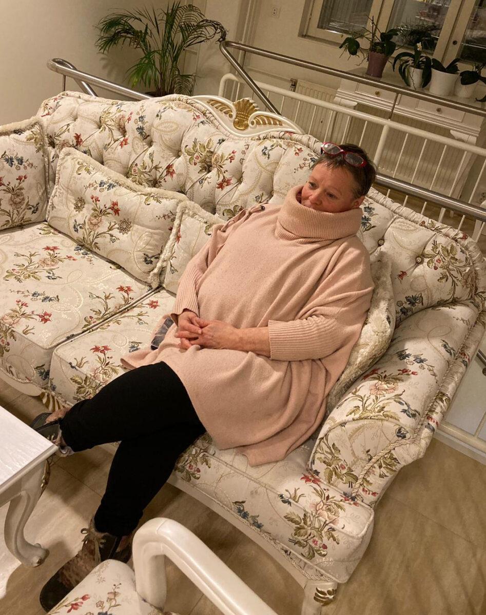 Nainen istumassa kukkasohvalla.